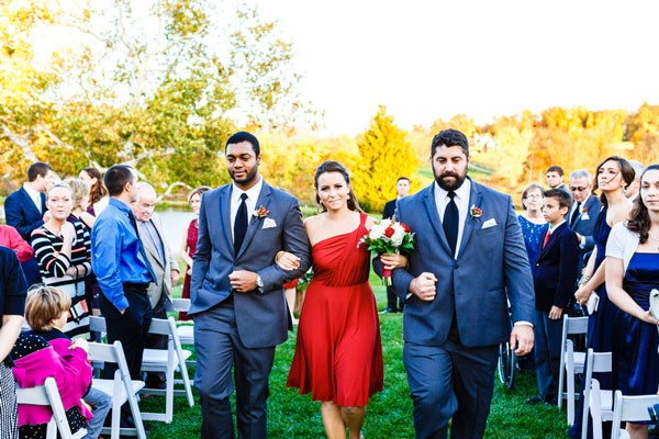 bridesmaid in scarlet dress with two groomsmen walking back down aisle
