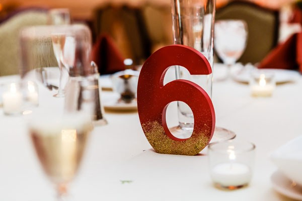 red table number dusted with gold glitter
