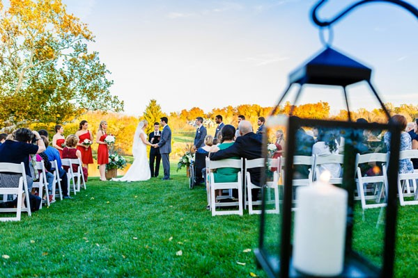 black lantern with candle lighting area behind chairs at outdoor ceremony