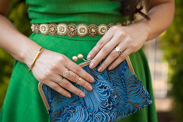 Green maid of honor dress with gold belt and blue clutch