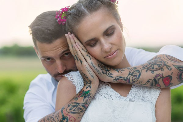 groom with sweet dream tattoes holds up his hands next to bride's head