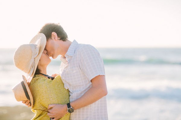 groom kisses engaged bride wrapped up in beach blanket