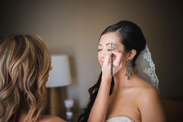 makeup artist highlighting bride's eyebrows before wedding