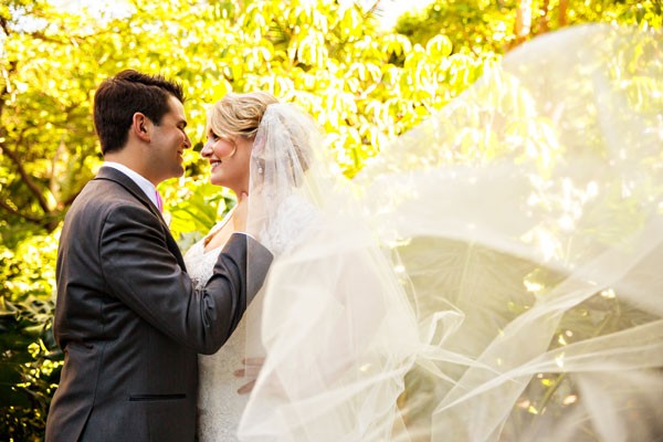 bride's veil blows in breeze at outdoor wedding
