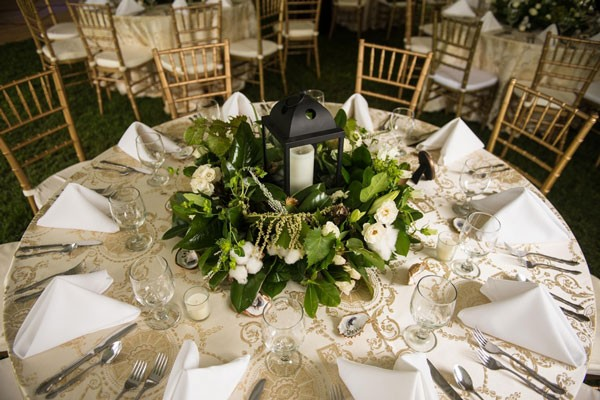 large wedding centerpiece with white flowers, greenery and black lantern over white linens