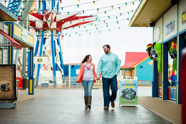 couple walks by games and concessions on Pleasure Pier in Galveston, TX