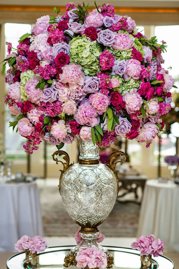 large wedding arrangement with pink, purple, and magenta flowers in silver urn