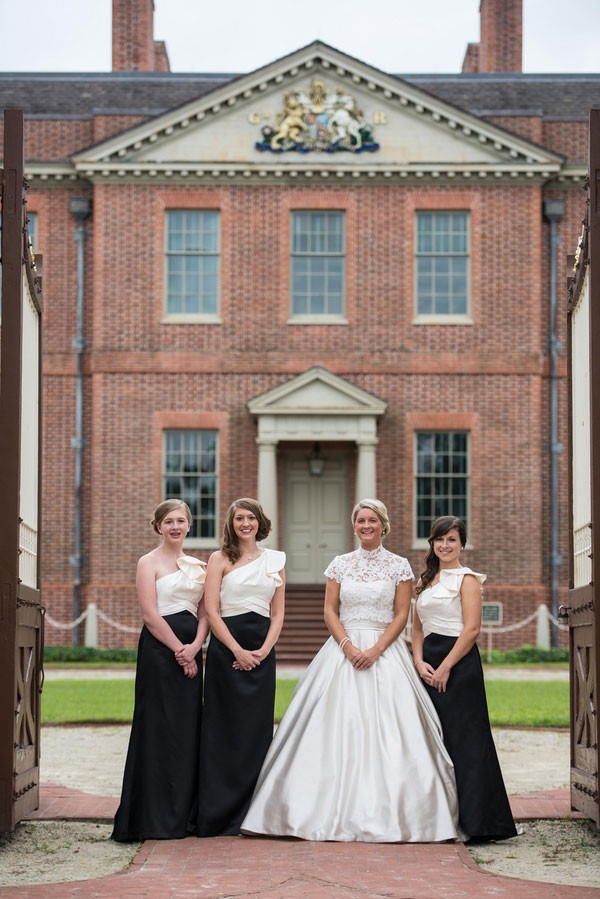 bridal party in black and white dresses with bride in front of brick estate