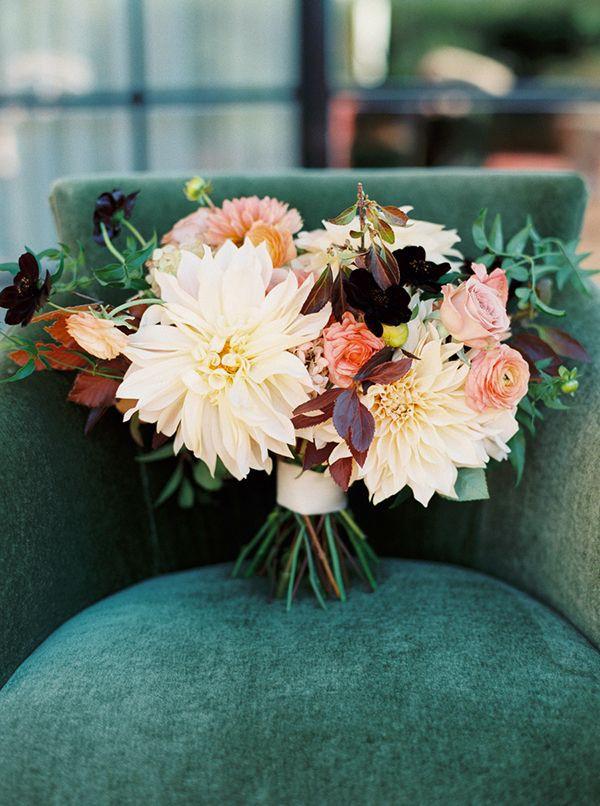 dahlia and ranunculus bridal bouquet sitting on velvet chair