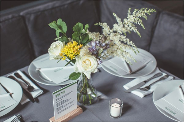 modern wedding table decor with gray linens, white plates and hints of yellow in centerpiece
