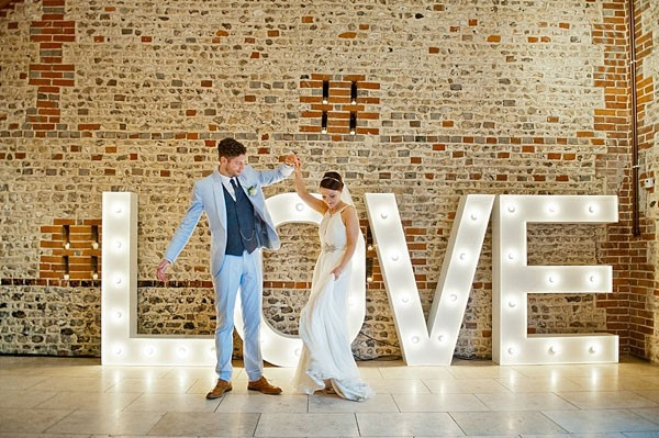 huge marquee love sign with bride and groom