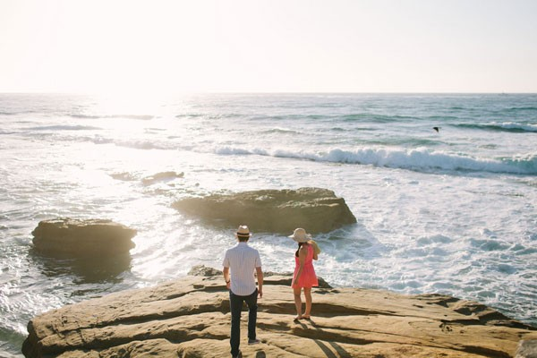couple stands on rocks by edge of Pacific Ocean coastline