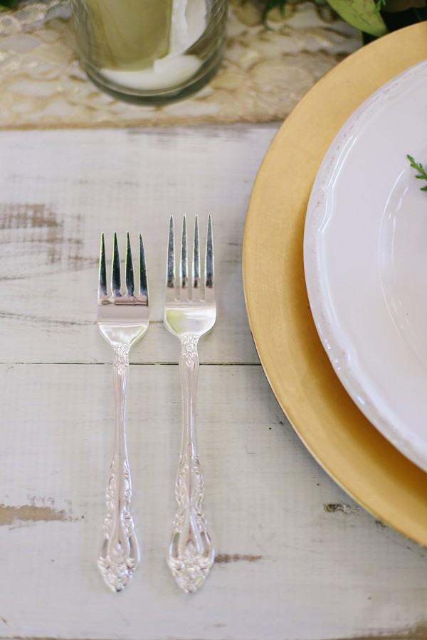 silver flatware next to gold charger and white plate