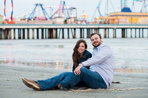 engagement session on beach in front of Pleasure Pier in Galveston, Texas