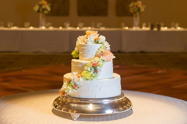 buttercream wedding cake with roses and hydrangea petals wrapped around layers