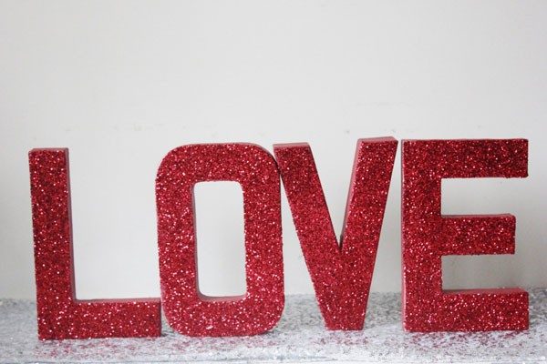 red glitter love sign in bold letters