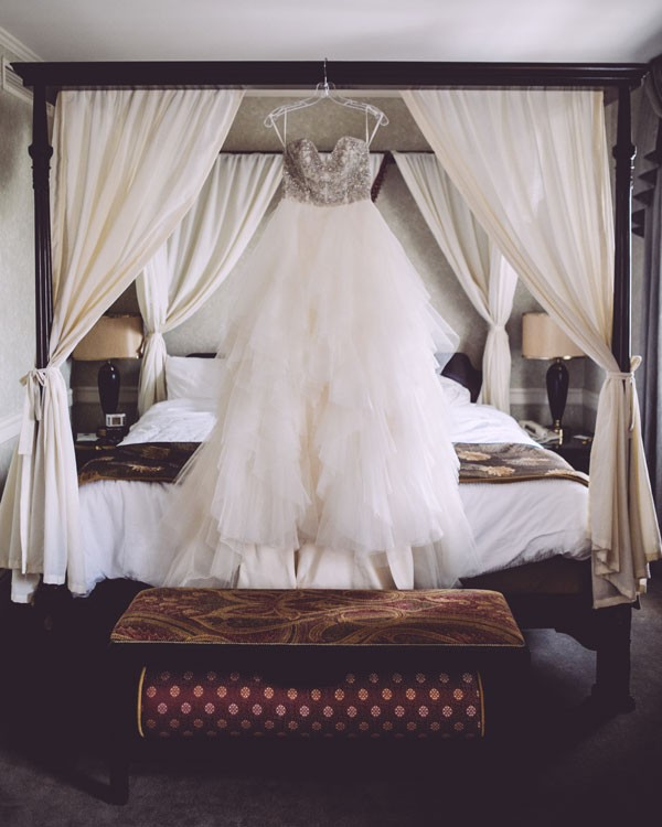 bustier style wedding dress hanging from bedframe