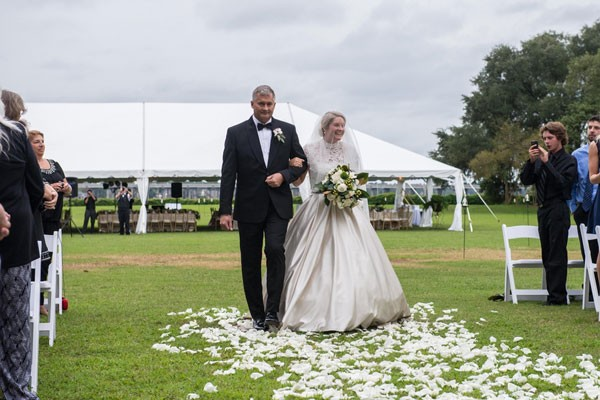 bride and father walk down white petal covered outdoor aisle
