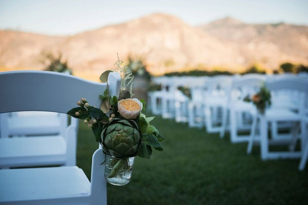 arrangement with peach peony and artichoke in Mason jar hanging from ceremony chairs