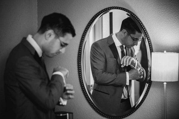 groom affixing cuff links in front of mirror in hotel room