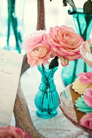 simple wedding centerpiece with pink roses and ranunculus in blue glass bud vase