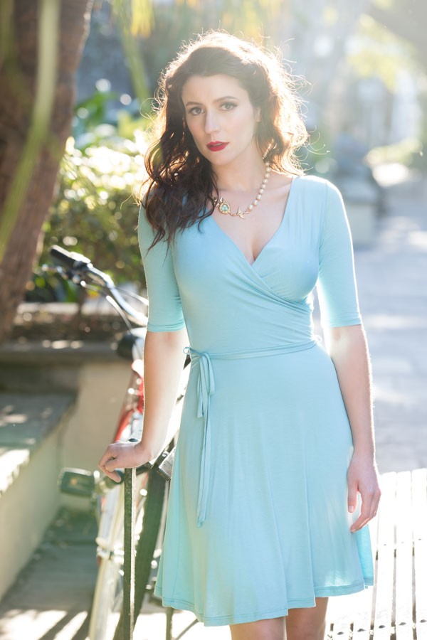 brunette bridesmaid in simple, pale aqua, wrap bridesmaid dress with loose bow