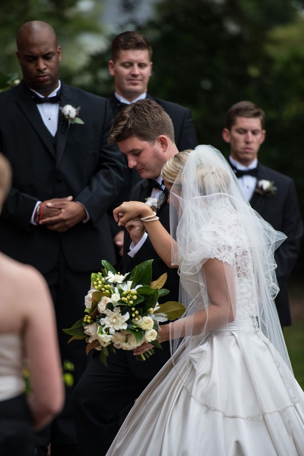 groom helps bride up brick steps for ceremony