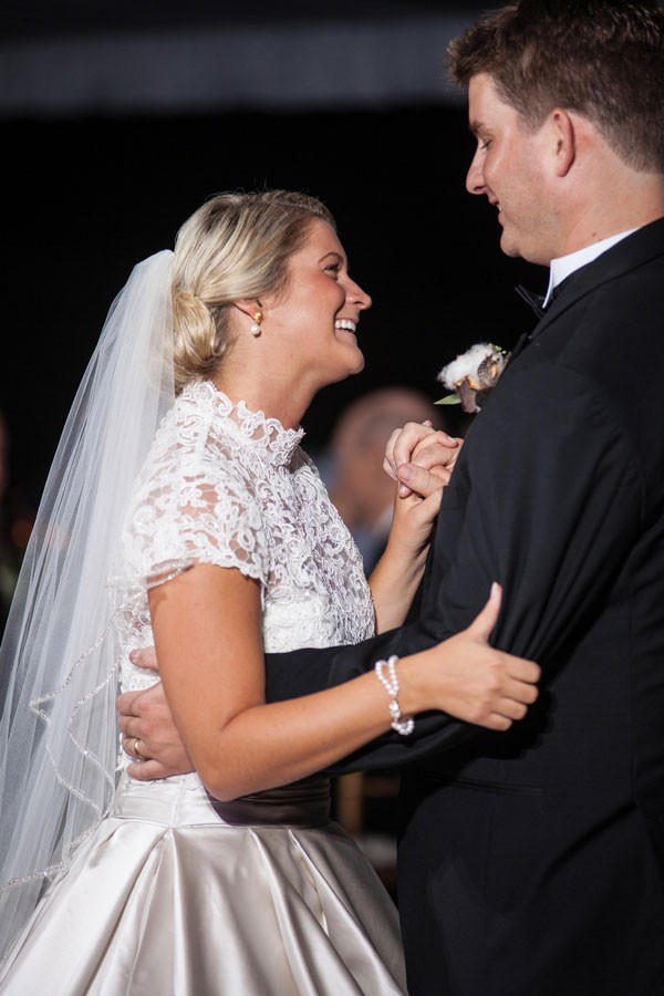 blonde bride with updo and veil dances with groom at reception