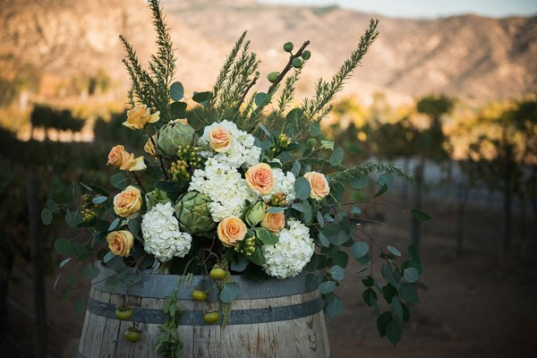 large arrangement filled with white hydrangeas, peach roses, and artichokes sitting on wine barrel