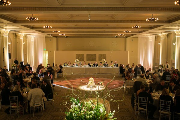wedding reception in ballroom with long table for wedding party