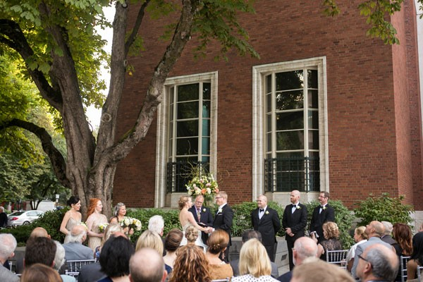 outdoor wedding ceremony under large tree by brick building
