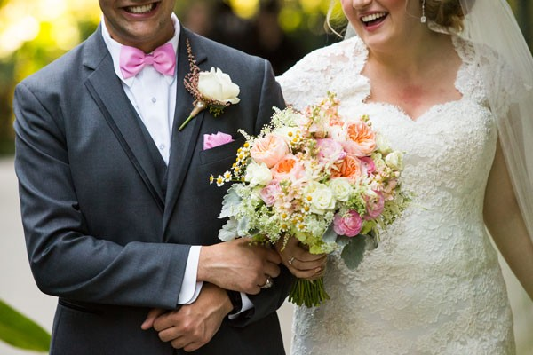 bride with pink and coral bouquet and groom with pink bow tie walking to ceremony