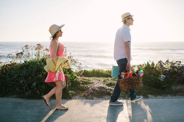 couple walk towards the beach with picnic baskets and blankets