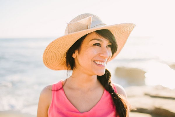 engaged woman stands on beach in coral dress and straw hat