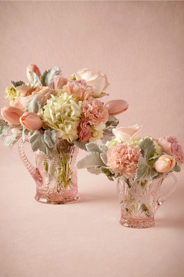 rosy hued wedding centerpiece with pale pink and cream flowers in rose glass pitcher