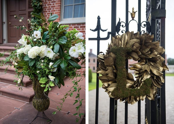 large floral arrangement on ceremony venue steps and monogram wreath hanging from steel gate