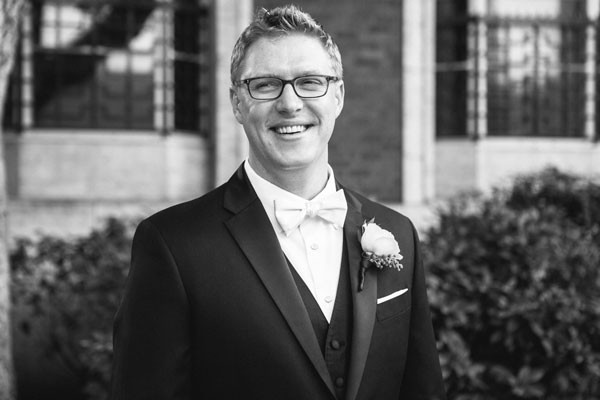 groom in black tuxedo with white bow tie