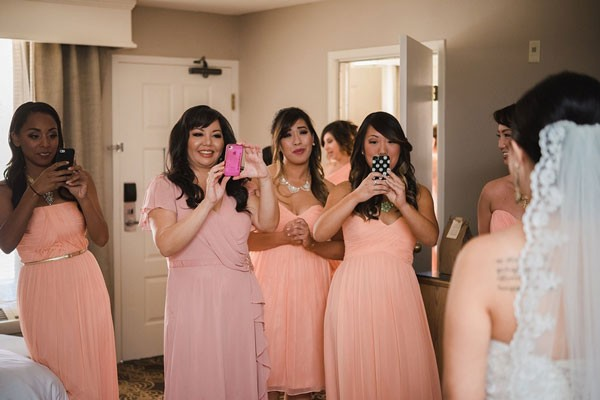 bridal party in peach and pink dresses taking first photos of bride getting ready