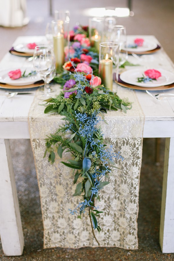 long bright flower wedding centerpiece on top of lace table runner