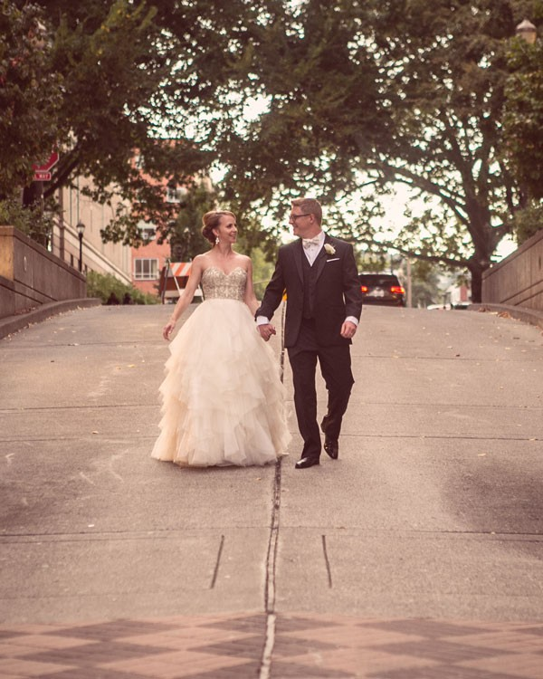 bride and groom walk down sidewalk in Portland, OR
