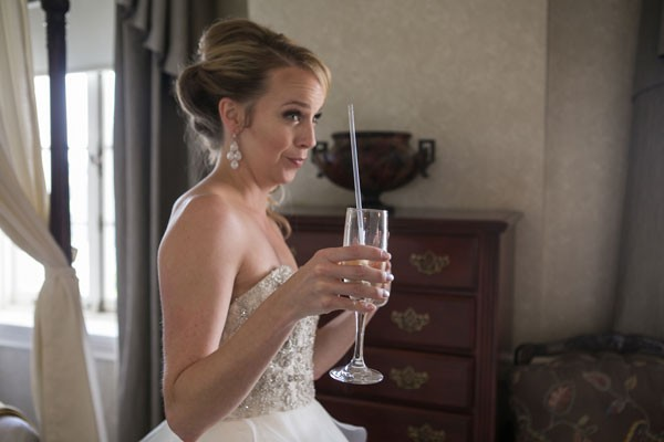 silly bride drinking champagne from glass with straw while making a goofy face