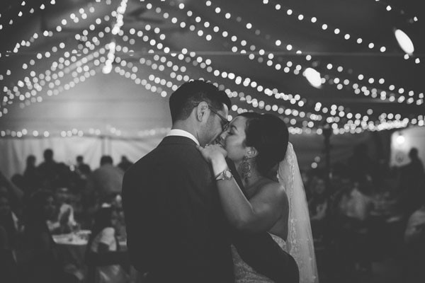 bride and groom dance under tent with string lights