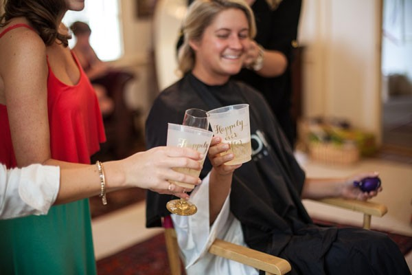 bride smiles and drinks champagne while getting ready for wedding