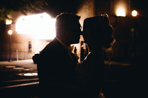 bride and groom kiss in the shadows
