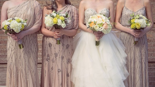 bridal party in one shoulder blush and silver bridesmaid dresses holding bouquets with bride