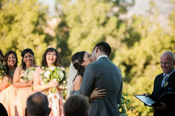 groom kisses bride with bridesmaid in pink dresses in background