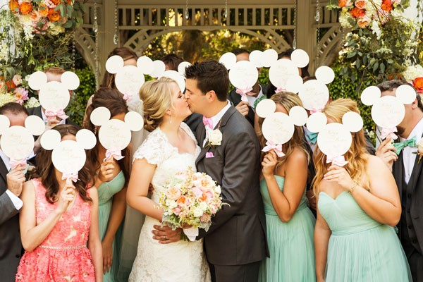 bride and groom kiss with guests' faces hidden by Mickey Mouse programs