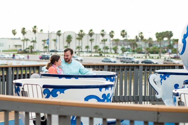 engaged couple on tea cup ride in Galveston, TX at Pleasure Pier