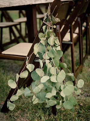 eucalptus leaves gathered and tied to backs of chairs of ceremony aisle