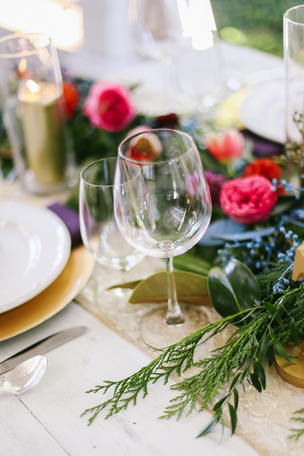 classic wine glasses in vintage wedding tablescape with bright flowers and gold details